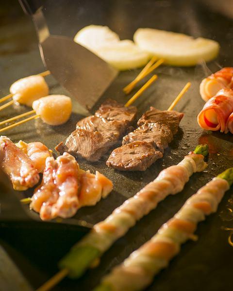 铁板烧盘子上的十串肉串(肉,海鲜,蔬菜)