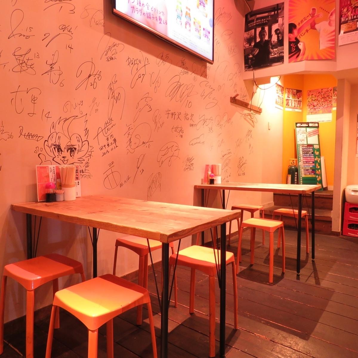 1Fにはテーブル席もご用意!壁には有名人やスポーツ選手のサインがズラリ!