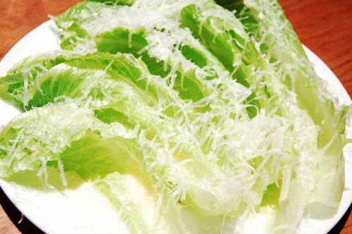 ガーリックをきかせたドレッシングと削りたてチーズをたっぷりかけたロメインレタスのシーザーサラダ