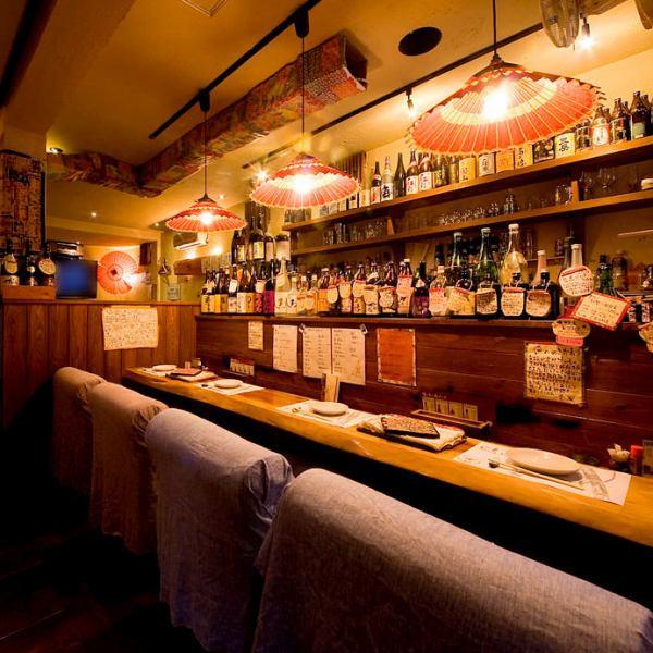 雰囲気あるライトがある【カウンター】。一枚板の【カウンターテーブル】でゆったり。 ふかふかの椅子と【カウンター】を埋め尽くすようにずらりと並んだお酒が自慢!!