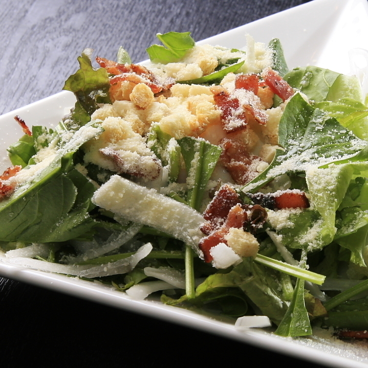 Caesar salad with raw ham and warm ball
