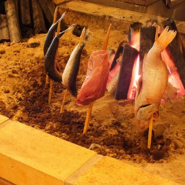 当店自慢の炭火焼を作る炉辺は店内中央に。オープンキッチンのため、注文した料理の調理風景を眺めながらご堪能いただけます。赤字覚悟でご提供する自慢のキンキの炭火焼は売り切れ御免!!