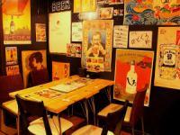 昭和を思わせるポスターに囲まれたテーブル席