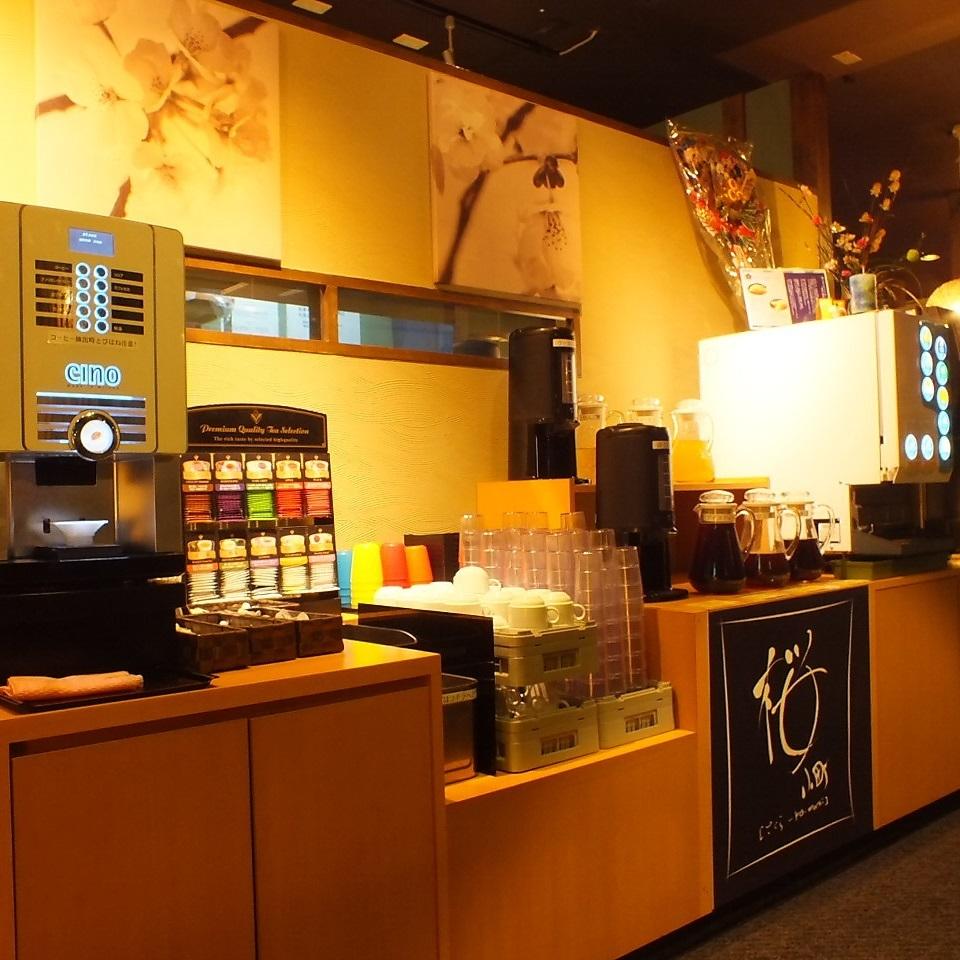 店内中央の種類豊富なドリンクバー : 健康をコンセプトにしてどりリンクバーは健康茶やりんご酢、アセロラなど種類豊富♪コーヒーも美味しいものにこだわってミラノから輸入したコーヒーマシンに厳選したコーヒー豆を使用しています。