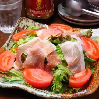 Caesar salad with raw ham and tomato